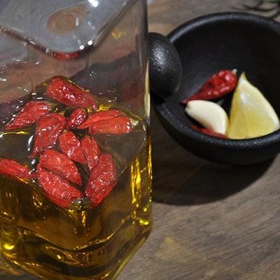 Würzen mit Chilischote Piri Piri in Olivenöl und frischem Knoblauch mit Zitronenscheibe
