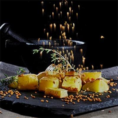 Würzen mit Bockshornklee gestreut auf Bratkartoffeln