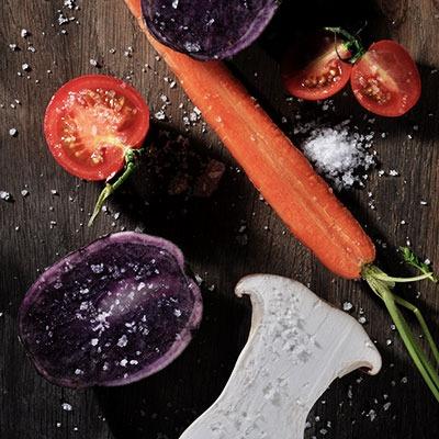 Würzen mit Fleur de Sel auf Rüben, Tomate, Karotte und Kräuterseitling