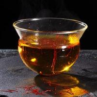 Würzen mit Safranfäden im warmen Teeglas