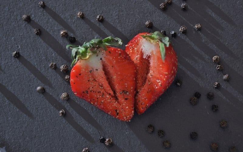 Obst und Gewuerze wie Pfeffer auf Erdbeere